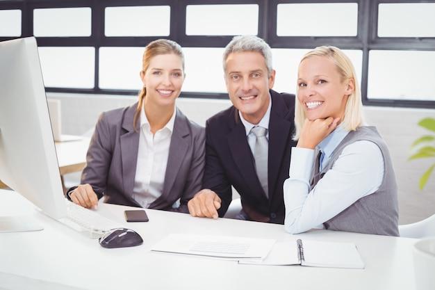 Porträt von den lächelnden geschäftsfachleuten, die am computertisch arbeiten