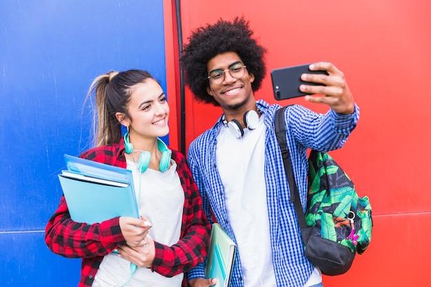 Porträt von den lächelnden jugendpaaren, die zusammen selfie auf mobiltelefon gegen farbige wand nehmen
