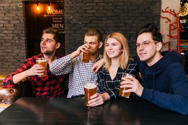 Porträt von den lächelnden jungen freunden, die das bier genießen