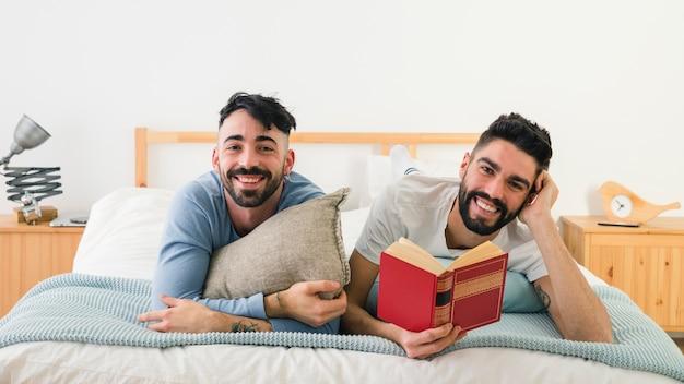 Porträt von den lächelnden jungen homosexuellen paaren, die auf front über dem bett liegen, das kamera betrachtet