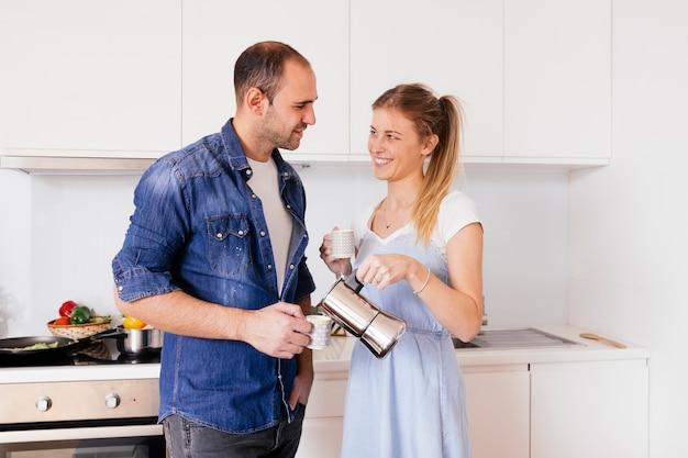 Porträt von den lächelnden jungen paaren, die den kaffee stehen in der küche trinken