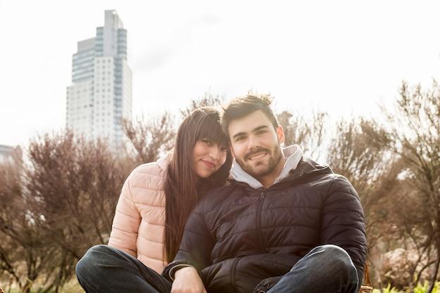 Porträt von den lächelnden jungen paaren, die im park sitzen