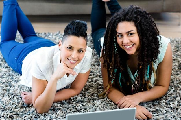 Porträt von den lächelnden lesbischen paaren, die auf wolldecke liegen und laptop im wohnzimmer verwenden