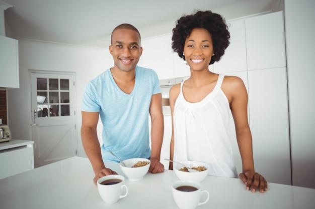 Porträt von den lächelnden paaren, die in der küche während des frühstücks stehen