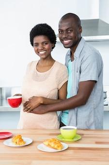 Porträt von den lächelnden schwangeren paaren, die zu hause in der küche frühstücken