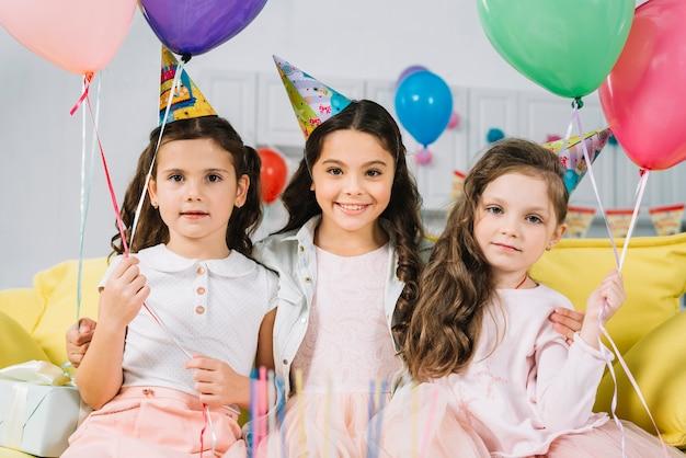 Porträt von den mädchen, die auf sofa mit bunten ballonen sitzen