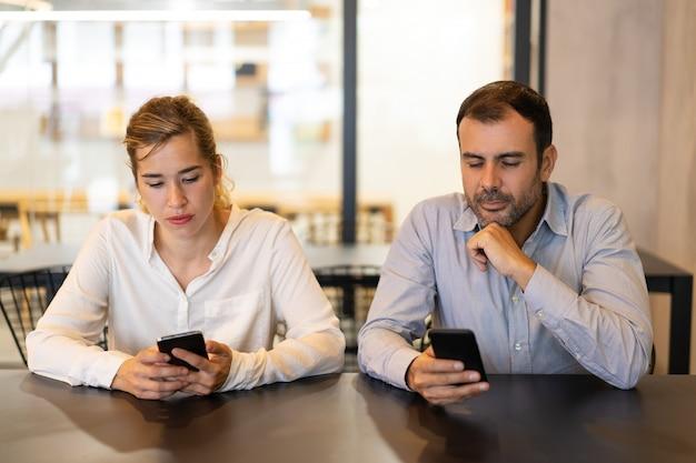 Porträt von den männlichen und weiblichen kollegen, die telefone am café verwenden