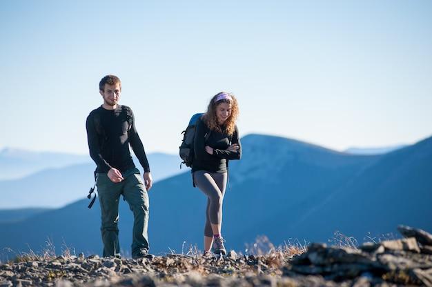 Porträt von den männlichen und weiblichen wanderern, die oben in die berge gehen