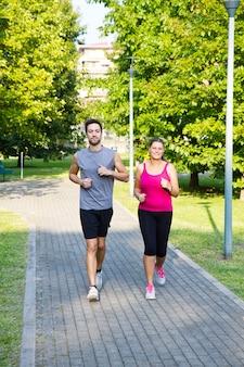Porträt von den netten kaukasischen paaren, die in den park laufen