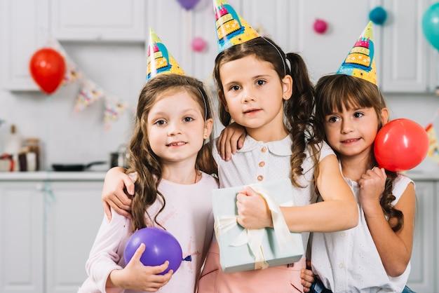 Porträt von den netten mädchen, die zusammen mit bunten ballonen und geburtstagsgeschenk stehen