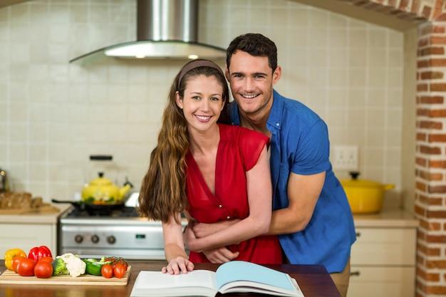 Porträt von den paaren, die in der küche bei der prüfung des rezeptbuches umfassen