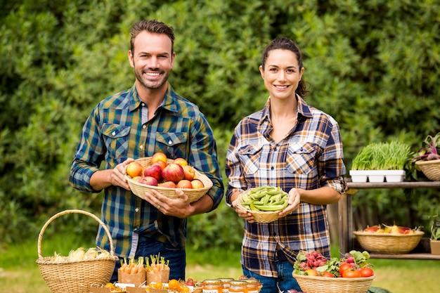 Porträt von den paaren, die organisches gemüse verkaufen