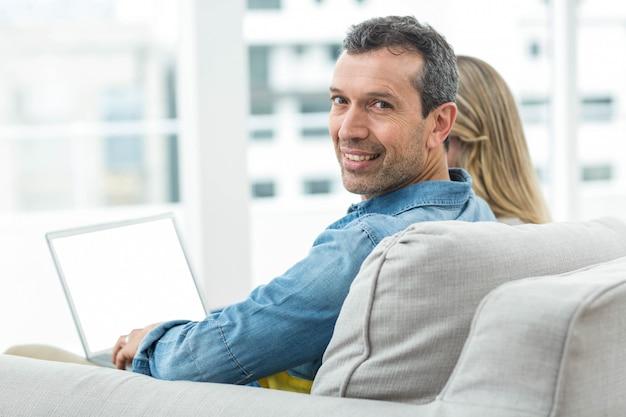 Porträt von den paaren, die zusammen auf sofa sitzen und laptop verwenden