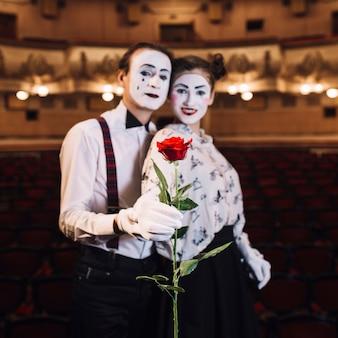 Porträt von den pantomimepaaren, die rotrose halten