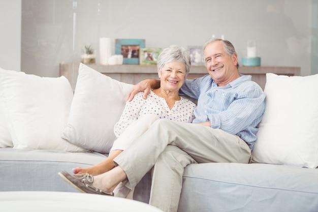 Porträt von den romantischen älteren paaren, die auf sofa im wohnzimmer sitzen
