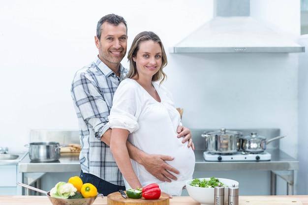 Porträt von den schwangeren paaren, die kamera in der küche betrachten