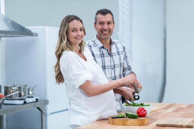Porträt von den schwangeren paaren, die salat in der küche zubereiten