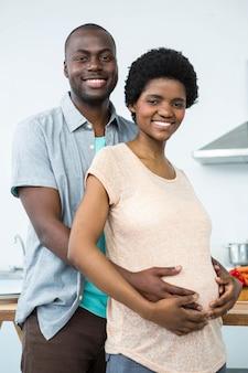 Porträt von den schwangeren paaren, die sich zu hause in der küche umfassen