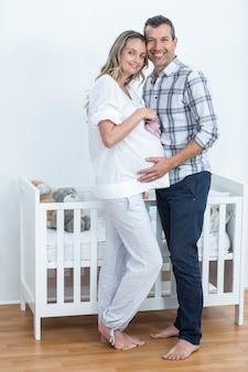Porträt von den schwangeren paaren, die zu hause babyschuhe halten