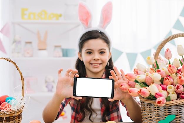 Porträt von den tragenden häschenohren eines mädchens, die ihren smartphone an ostern-tag zeigen
