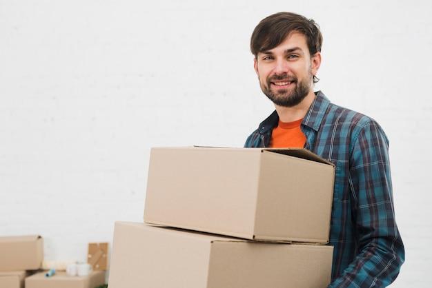 Porträt von den tragenden pappschachteln eines jungen mannes, die zur kamera gegen weißen hintergrund schauen