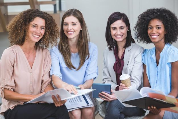 Porträt von den weiblichen geschäftskollegen, die zusammen mit dokument sitzen