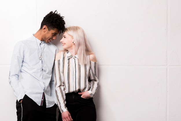 Porträt von den zwischen verschiedenen rassen lächelnden jugendpaaren, die einander betrachten