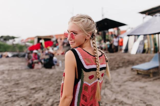 Porträt von der rückseite der blonden frau im gestrickten trägershirt, das mit lächeln aufwirft. außenaufnahme der stilvollen dame mit zöpfen, die zeit am strand verbringen.