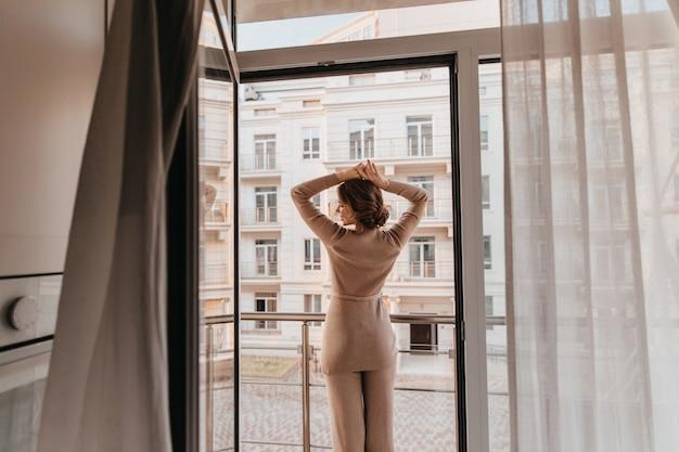 Porträt von der rückseite der entspannten frau im braunen outfit. foto der fröhlichen stilvollen dame, die nahe großes fenster aufwirft.