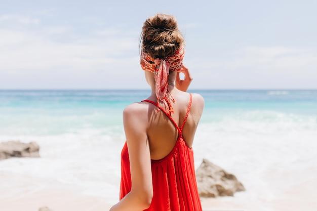 Porträt von der rückseite der romantischen jungen dame trägt rote kleidung während der ruhe am strand. außenaufnahme des glückseligen mädchens, das meerblick genießt.