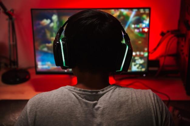 Porträt von der rückseite des jugendlichen spielerjungen, der bildschirm betrachtet und videospiele auf computer in dunklem raum trägt, der kopfhörer trägt
