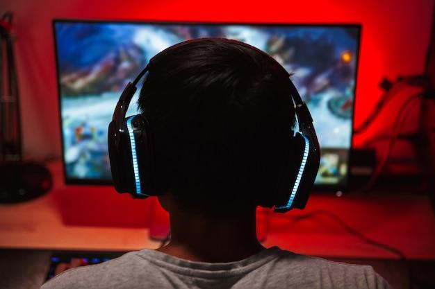 Porträt von der rückseite des jungen spielers, der auf bildschirm schaut und videospiele auf computer in dunklem raum trägt, der kopfhörer trägt