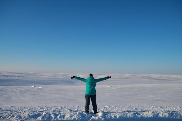 Porträt von der rückseite einer warm gekleideten frau in defokussierung, die vor dem meer steht und weit weg schaut und in zeitlupe auf das raue wasser des winters blickt
