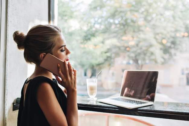 Porträt von der seite hübsche frau im schwarzen kleid in der cafeteria. sie telefoniert und schaut auf einen laptop.