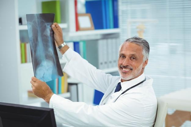 Porträt von doktor einen röntgenstrahlbericht in der klinik überprüfend