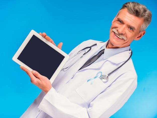 Porträt von doktor mit dem blauen band, welches die tablette hält.