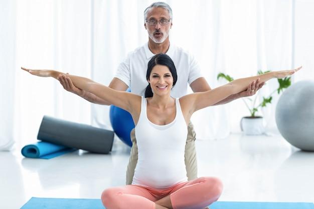 Porträt von doktor physiotherapie der schwangeren frau überprüfend und gebend