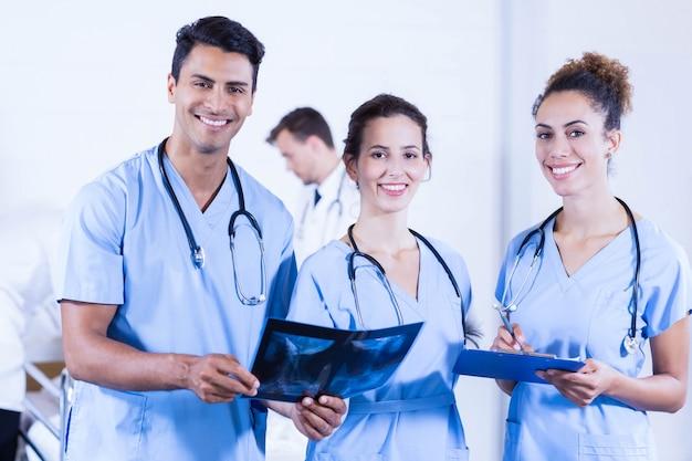 Porträt von doktoren, die einen röntgenstrahlbericht halten und im krankenhaus lächeln