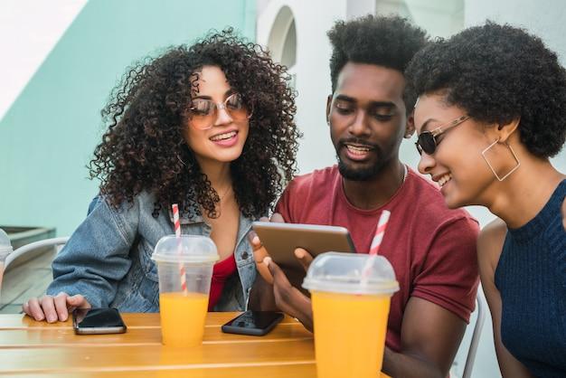 Porträt von drei afro-freunden, die zusammen spaß haben und digitales tablet im freien in einer cafeteria verwenden. technologiekonzept.