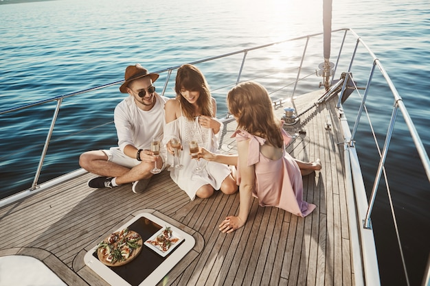 Porträt von drei attraktiven europäischen leuten, die an bord der yacht sitzen und das abendessen genießen, während sie champagner trinken und fröhlich sprechen. freunde haben das ganze jahr hart gearbeitet, um endlich sonne und meer zu genießen