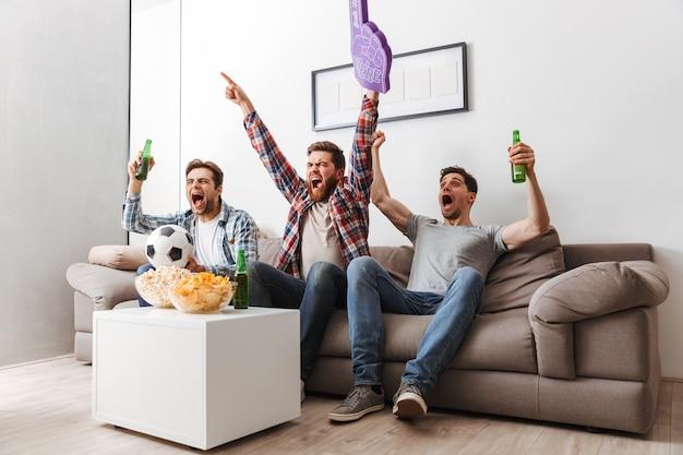 Porträt von drei aufgeregten jungen männern, die fußball schauen, während sie zu hause mit bier und snacks drinnen sitzen