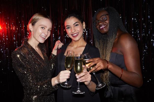 Porträt von drei eleganten jungen frauen, die champagnergläser halten und in die kamera lächeln, während sie gegen funkelnden hintergrund auf partei aufwerfen, mit blitz geschossen