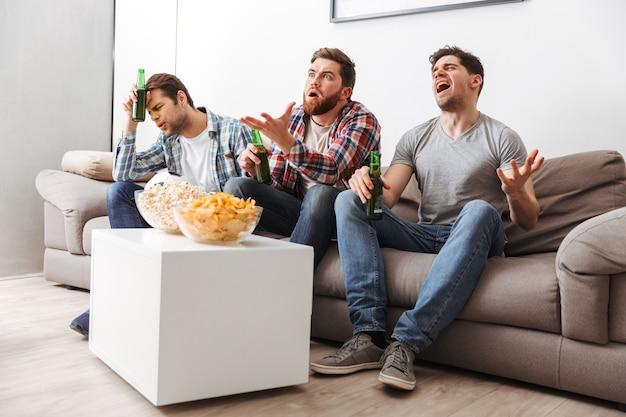Porträt von drei enttäuschten jungen männern, die fußball schauen, während sie zu hause mit bier und snacks drinnen sitzen