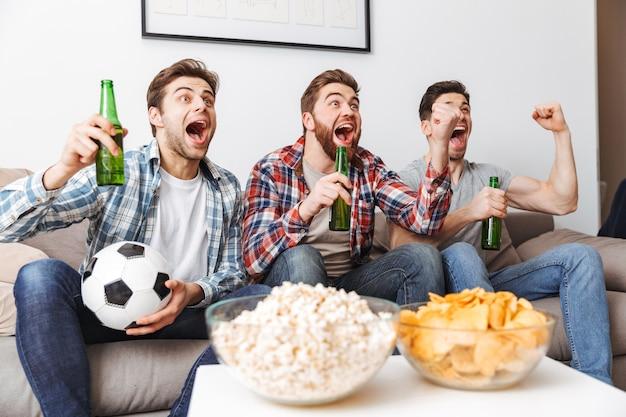 Porträt von drei freudigen jungen männern, die fußball schauen, während sie zu hause sitzen, bier trinken und snacks essen