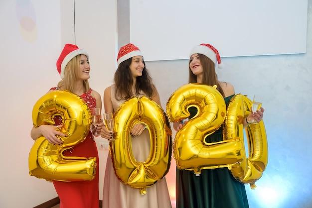Porträt von drei fröhlichen, glücklichen mädchen in eleganten kleidern, die mit goldfarbenen zahlenballons posieren. neujahr, weihnachten