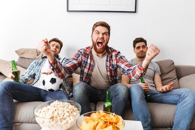 Porträt von drei fröhlichen jungen männern, die fußball schauen, während sie zu hause mit bier und snacks drinnen sitzen