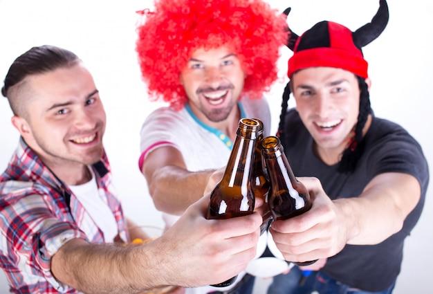 Porträt von drei fußballfans feiern gewinn.