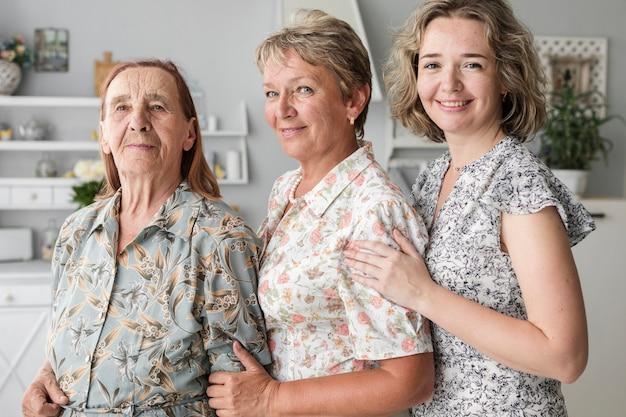 Porträt von drei generationsfrauen, welche die kamera zusammen steht betrachten