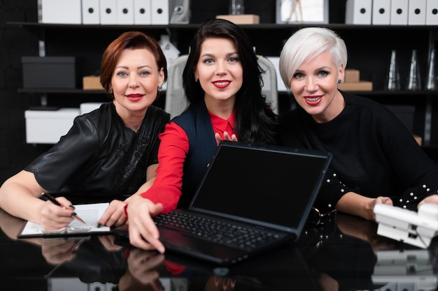 Porträt von drei geschäftsfrauen bei der arbeit im stilvollen büro