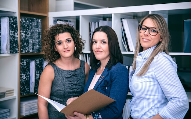 Porträt von drei geschäftsfrauen, die im büro arbeiten und in die kamera lächeln